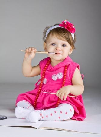 bebe sentado: Chica sentada sosteniendo un peque�o pincel, sobre un fondo oscuro Foto de archivo