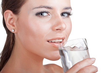 Wet beautiful woman drinks water from a glass, isolated on white background