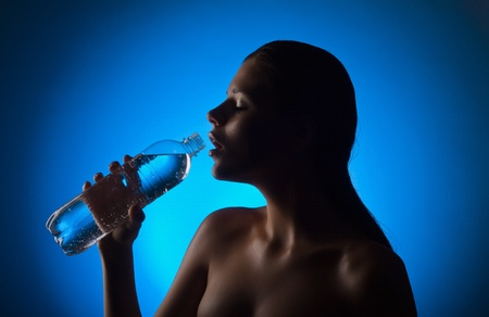 Beautiful woman holding a bottle of water on a blue background photo