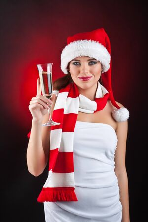 A beautiful woman dressed in a Christmas holding a glass of champagne, on dark background photo