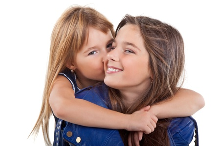 Little girl kissing her sister, isolated on white background Stock Photo