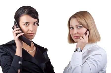 Two business women talking on mobile phone, isolated on white background photo