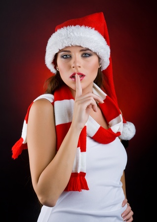 quietly: Beautiful girl in the New Year costume shows a gesture of quiet, on dark background