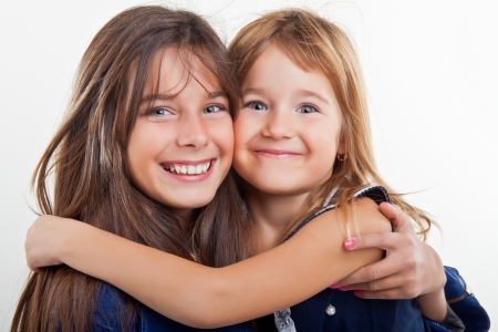 interacting: Two young sister smiling together on white background