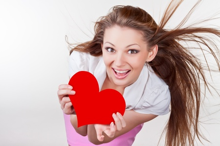 Smiling young woman holding a heart, isolated on white background photo