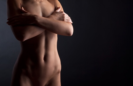 Beautiful naked female body, on a dark background