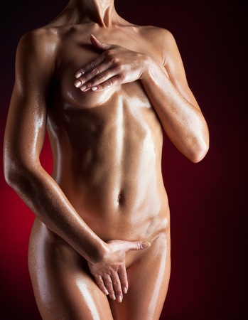 Naked woman in the oil covers himself with his hands, on a dark background