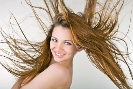 cheerful young woman with developing hair, on a light background Stock Photo - 11860370