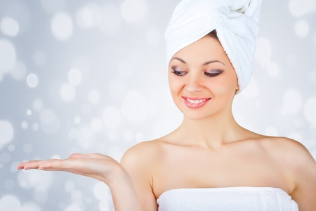 Portrait of beautiful woman wrapped in the bath towel showing something on the palms of her hands, on a light background photo