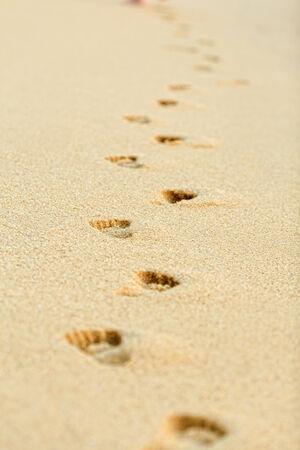 spoor: Footprints on yellow sand on the seashore