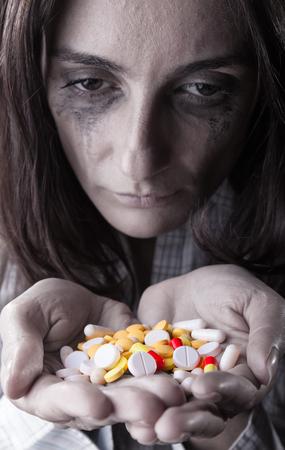 diseased: Pills in womens hands on dark background. Focus on pills