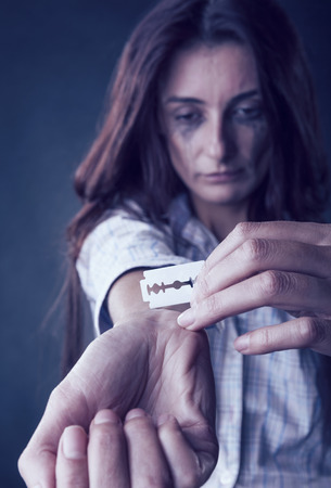 Young woman cuts veins on a hand on a dark background. Focus on hand photo