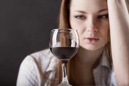 tomando alcohol: Mujer hermosa joven en la depresi�n, el consumo de alcohol en el fondo oscuro Foto de archivo