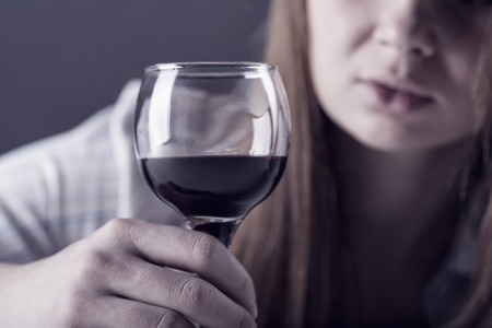 drug addiction: Young beautiful woman in depression, drinking alcohol on dark background