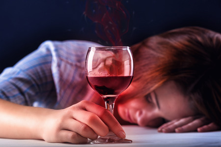 forlorn: Young beautiful woman in depression, drinking alcohol on dark background
