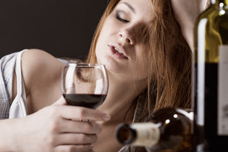 Young beautiful woman in depression, drinking alcohol Stock Photo