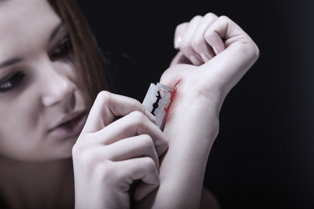 razor blade: Young woman cuts veins on a hand on a dark background. Focus on hand
