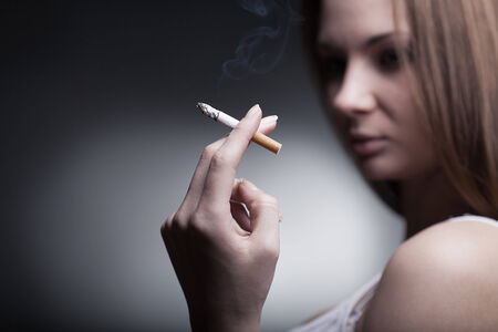 mortal danger: A woman with a cigarette on a dark background. Focus on cigarette Stock Photo
