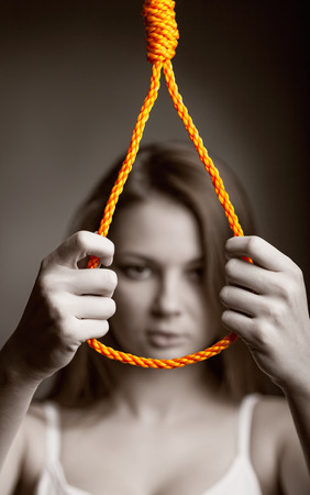 Young woman wants to hang on a dark backgroundю Focus on the rope photo