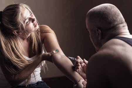 illicit: Young couple addicts. Man injects girlfriend drug into a vein Stock Photo