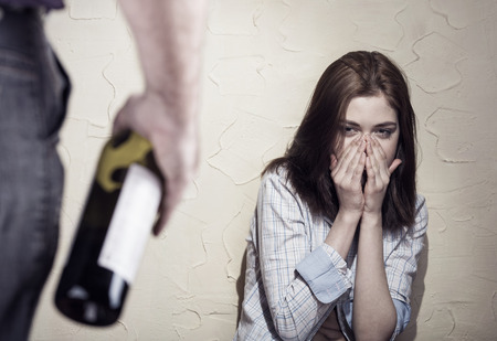 violence: Woman victim of domestic violence and abuse. Woman scared of a man holding a bottle