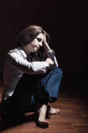mujer golpeada: Triste mujer sentada sola en una habitaci�n vac�a Foto de archivo