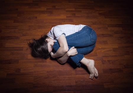 mujer golpeada: Tirado en el piso de una joven solitaria en una habitación vacía