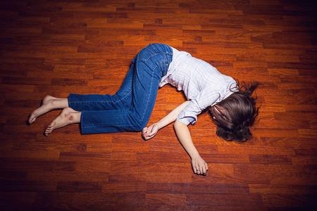 mujer golpeada: Chica acostado en el piso en una habitación vacía