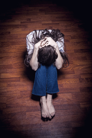 battered woman: Sad woman sitting alone in a empty room
