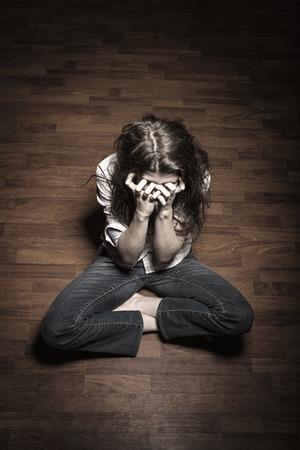 mujer golpeada: Triste mujer sentada sola en una habitación vacía Foto de archivo