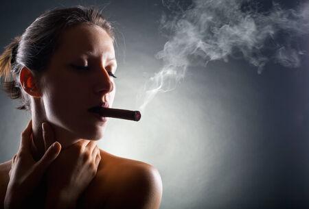 doses: Vrouw met sigaar Uitademen rook op een donkere achtergrond