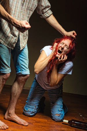 The man grabbed his wife by the hair with the requirements to stop drinking alcohol Stock Photo