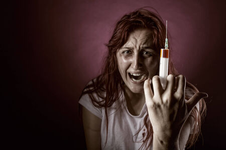 Weeping Woman addict. Focus on the syringe Stock Photo