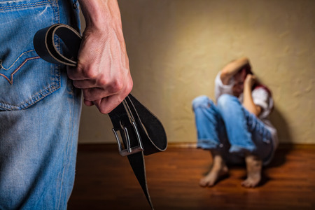 sexual violence: Woman victim of domestic violence and abuse. Husband intimidates his wife. Focus on the arm with a belt