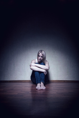 battered: Young sad woman sitting alone on the floor in an empty room