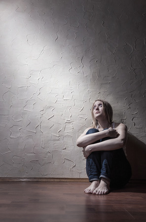 Young sad woman sitting alone on the floor in an empty room photo