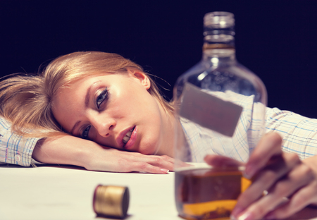 drug addict: Young beautiful woman in depression, drinking alcohol Stock Photo