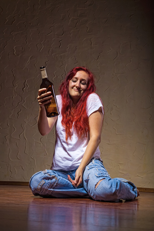 intoxicated: A young woman from a bottle of wine-drinking at home sitting on the floor