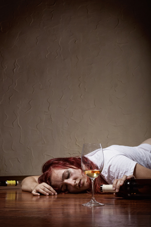 Drunken young woman lying on the floor. Focus on glass Фото со стока