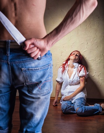 holding a knife: Woman victim of domestic violence and abuse. Husband holding a knife intimidates his wife