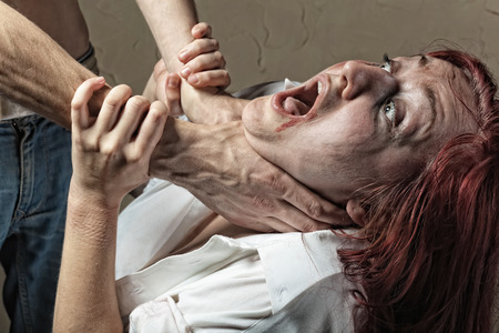 Victim of domestic violence. Husband strangles his wife, she cries 스톡 콘텐츠