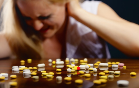 sick person: Pills lying on the table before suffering from the pain the young woman