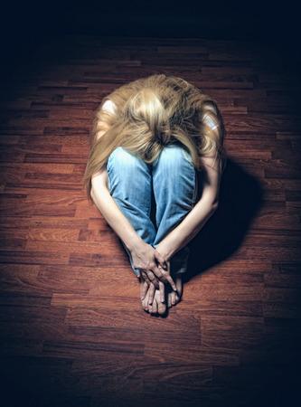 femme triste: Sad woman assis seul dans une salle vide