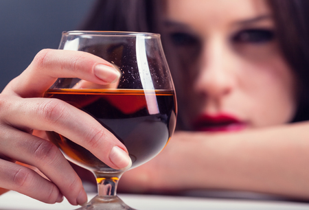 alcohol abuse: Woman in depression, drinking alcohol. Focus on glass Stock Photo