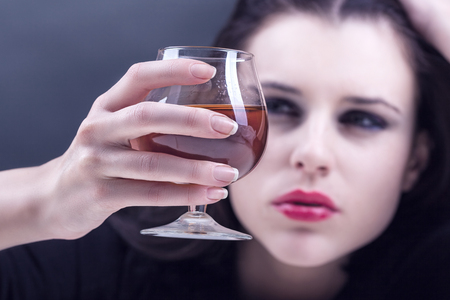 alcohol addiction: Young beautiful woman in depression, drinking alcohol on dark background. Focus on the glass
