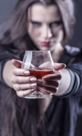 jovenes tomando alcohol: Mujer joven en la depresión, el consumo de alcohol. Centrarse en vidrio