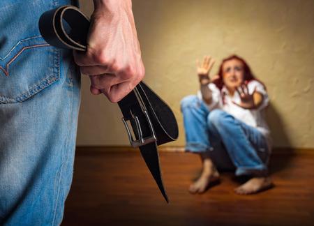 violencia intrafamiliar: Mujer v�ctima de violencia dom�stica y el abuso. Marido intimida a su esposa. Conc�ntrese en el brazo con una correa Foto de archivo