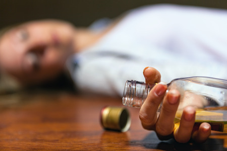 intoxicated: Drunken young woman lying on the floor. Focus on the bottle
