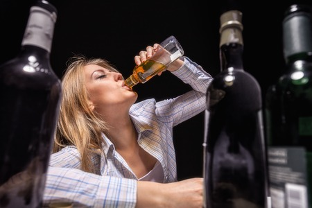 Young beautiful woman in depression, drinking alcohol Imagens