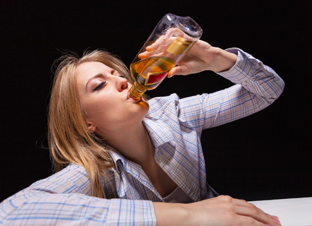 drinking alcohol: Young beautiful woman in depression, drinking alcohol Stock Photo